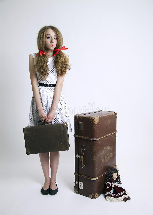 Doll-like girl with old suitcase royalty free stock photo