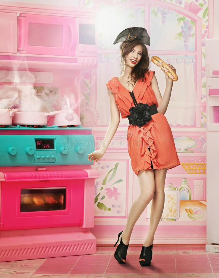 Doll like woman. In doll house kitchen stock image