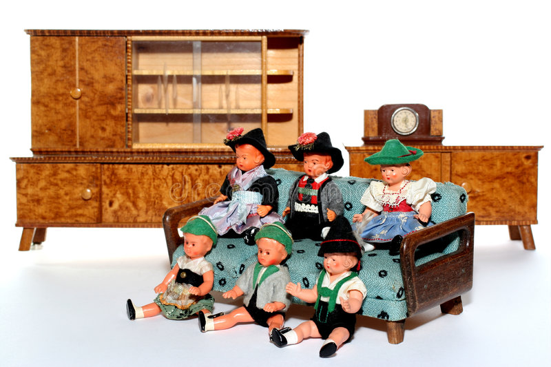 Doll meeting #8. 6 dolls in traditional European (I think they are Austrian but not sure) dresses sitting on a couch (old hand made furniture) with racks on the royalty free stock photo