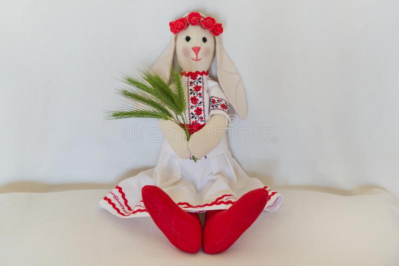 Doll in the national Ukrainian folk costume, keeps the spikelets. Handmade Bunny Rabbit sits on a light background royalty free stock photos