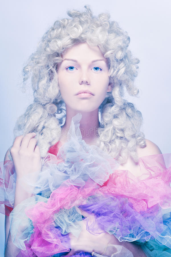 A doll or a princess. Cold tones photo. Cold tones photo. Girl with royal wig royalty free stock photography