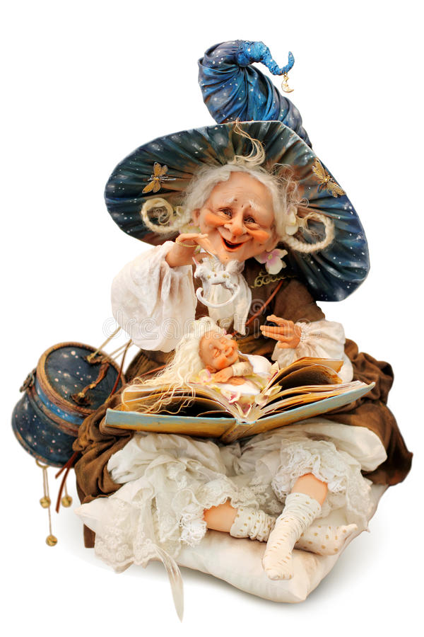 Doll Sorceress. Reading magic book, making magic or witchcraft and evoking dream. Isolated on a white background royalty free stock images