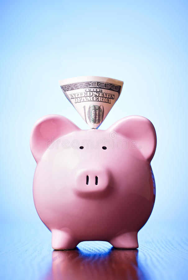 Dollar banknote in the slot of a piggy bank. Dollar banknote in the slot of a pink ceramic piggy bank on a blue background with a highlight for copyspace in a stock image