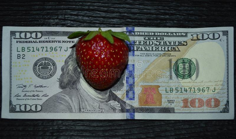 100-dollar banknote with strawberries on the site of Franklin`s face stock photos