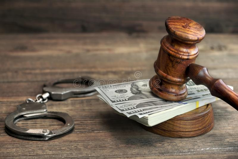 Dollar banknotes, handcuffs and judge gavel on wood table. USA Dollar Money Cash, Real Handcuffs And Judge Gavel On Rough Wood Background. Concept For Arrest stock images