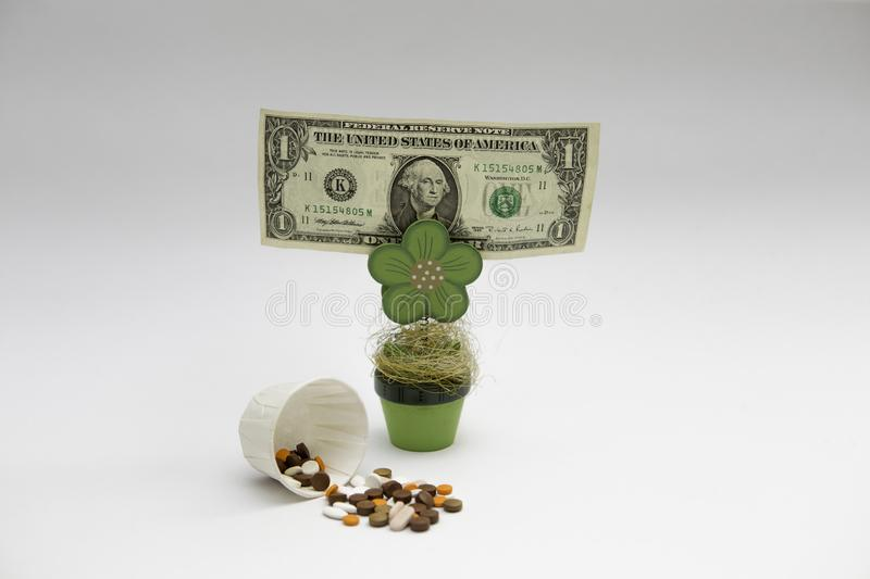 A dollar bill hold by wooden flower next to a spill tablets at the white background royalty free stock photography