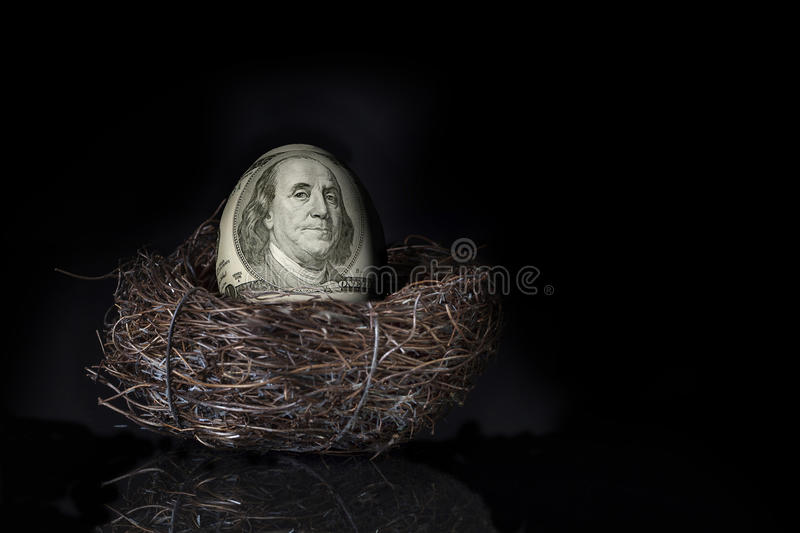 100 Dollar Bill Nest Egg. A US 100 dollar bill with face of Benjamin Franklin covering egg in nest, a concept for saving for retirement stock image
