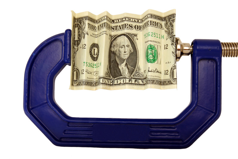 Dollar bill pinched in clamp. Financial or economic metaphor: dollar bill in clamp stock image