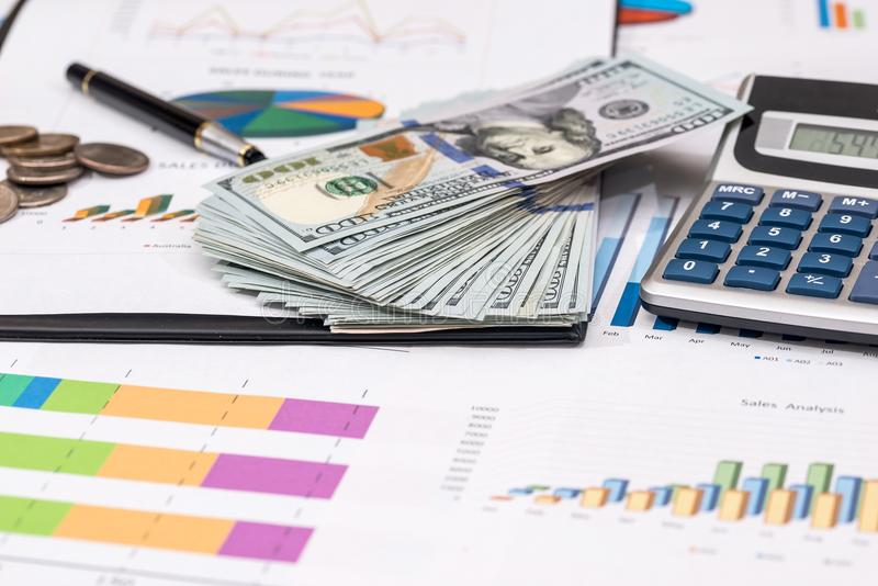 Dollar bills, coin on stock chart, calculator. And pen stock photography