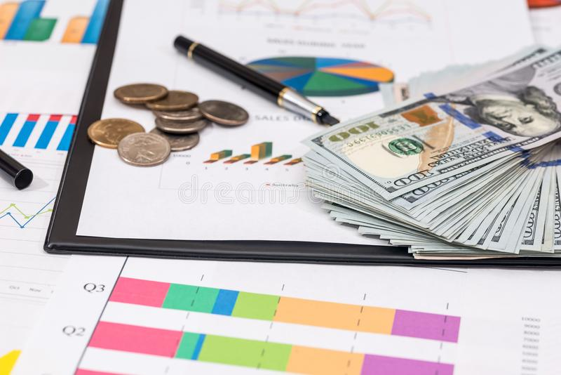 Dollar bills, coin on stock chart, calculator. And pen stock image
