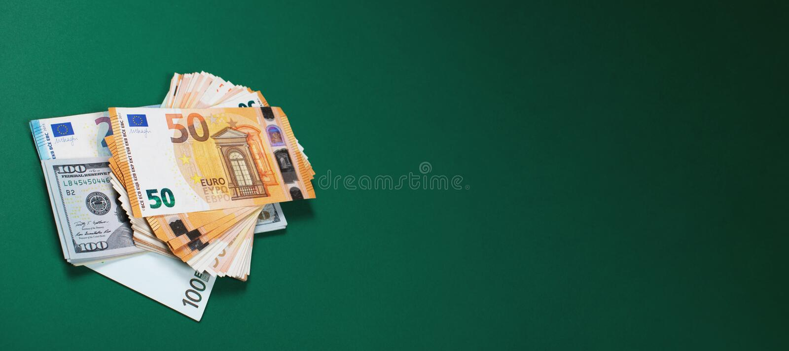 Dollar bills and euro notes on green background. stock images