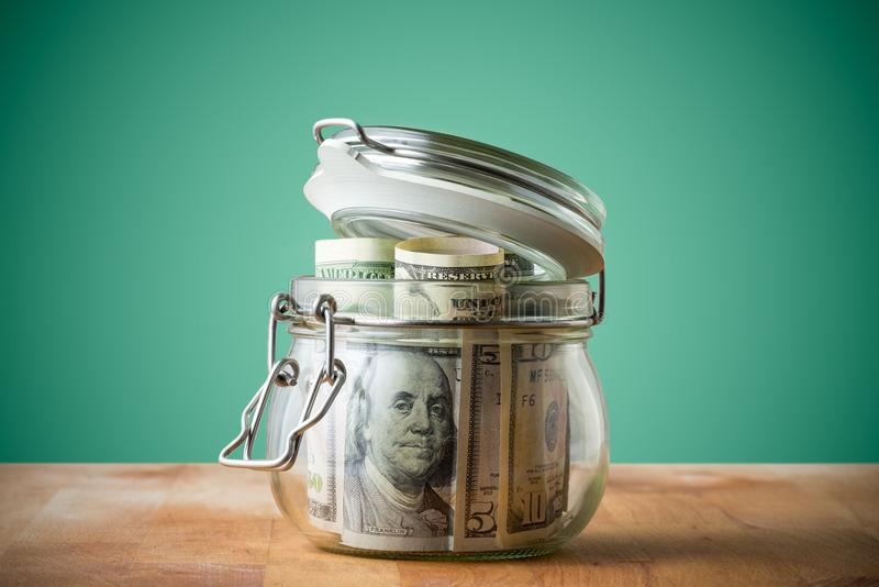 Dollar bills in glass jar isolated on a green background. stock images