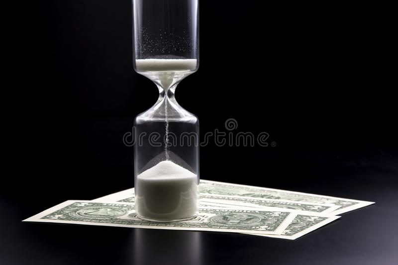 Dollar bills lie near the hourglass. Time is money. The salary. Business solutions in time. Hourglass time measurement. The Dollar bills lie near the hourglass royalty free stock image