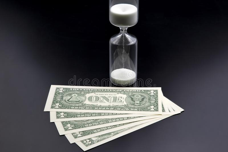 Dollar bills lie near the hourglass. Time is money. The salary. Business solutions in time. Hourglass time measurement. The Dollar bills lie near the hourglass royalty free stock photography