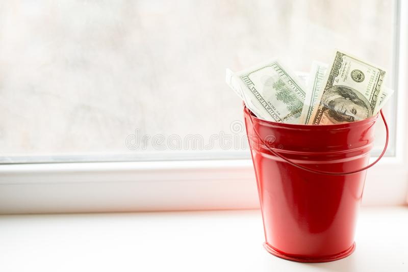 Dollar bills in red pail. on white window.light background. place for text. top view. a lot of money.  royalty free stock image