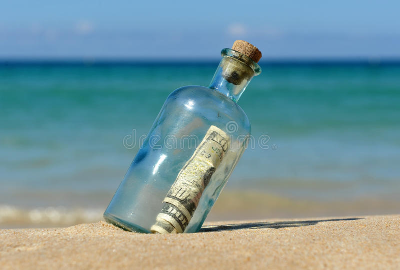 10 dollar in a bottle on the beach stock image