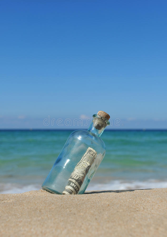 10 dollar in a bottle on the sand stock photography