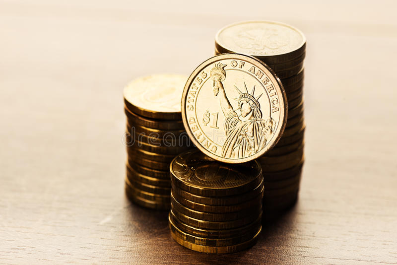 Dollar coin and gold money on the desk. One dollar coin and gold money on the desk royalty free stock photo