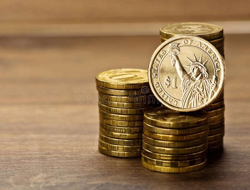Dollar coin and gold money. One dollar coin and gold money on the desk royalty free stock photography
