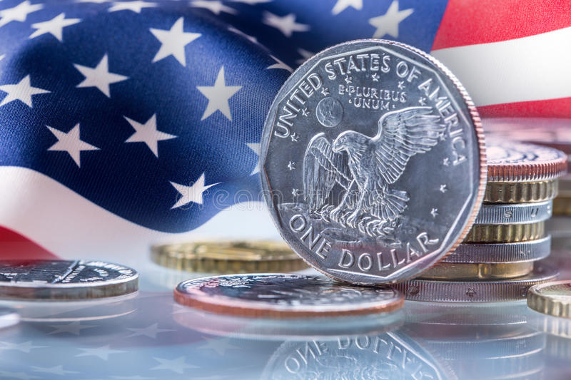 Dollar coins and USA flag in the background. USA Dollar coins standing on edge supported on coins royalty free stock image