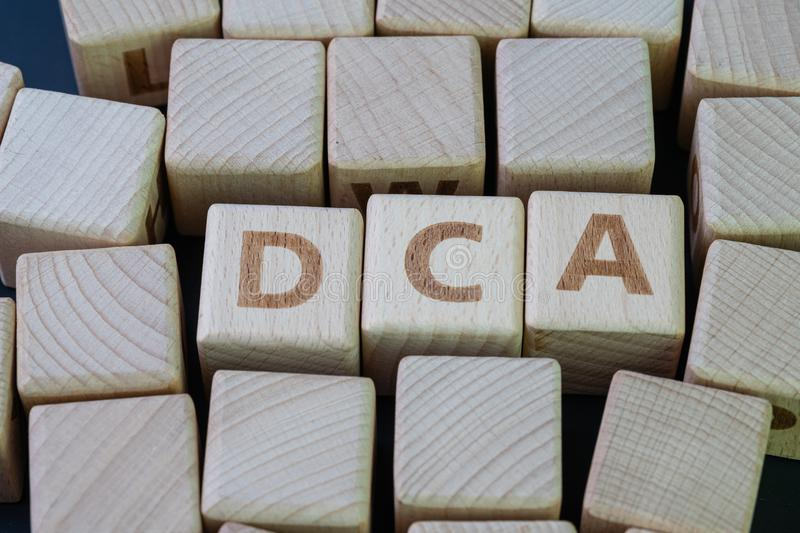 Dollar cost averaging DCA, investment strategy with the goal of reducing the impact of volatility concept, cube wooden block. With alphabet combine the word DCA stock images