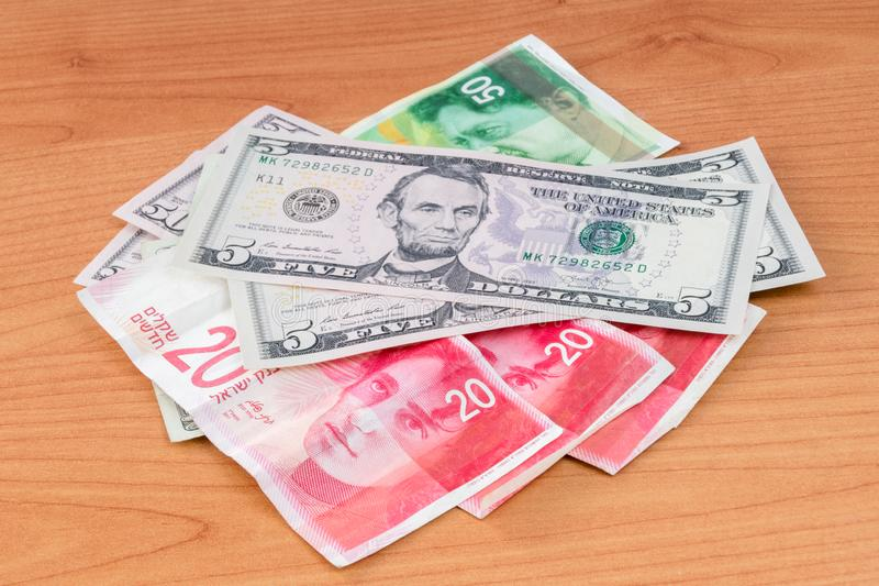 Dollar d'Etats-Unis et nouveaux billets de banque israéliens de shekel sur la table en bois photo libre de droits