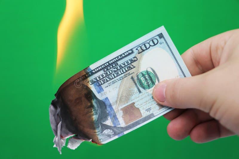 100 Dollar, die auf einem grünen Hintergrund brennen Konzept des Abwärtstrends bei der Wirtschaft und beim Verlust lizenzfreies stockfoto
