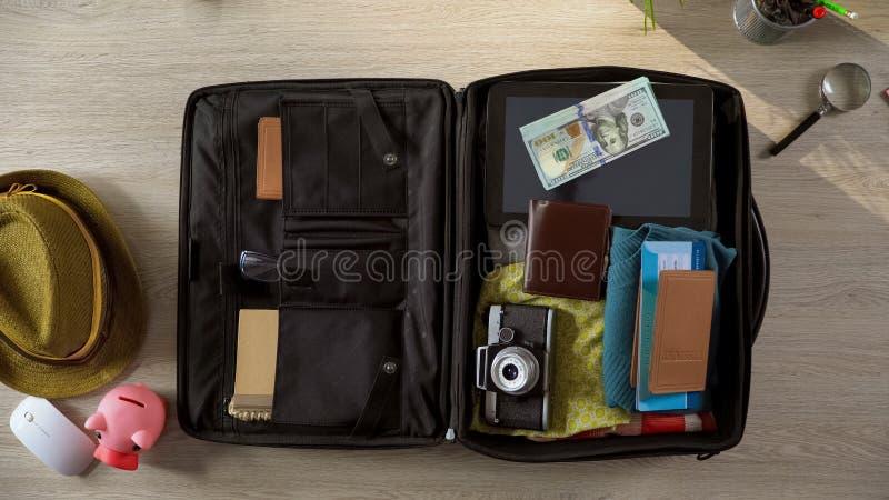 Dollar dokumenterar och kläder som utomlands packas i resväskan, lyxigt semesterlopp royaltyfri bild