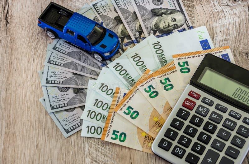 Dollar, euro, en räknemaskin och en blå bil för leksak på en träbakgrund arkivbild