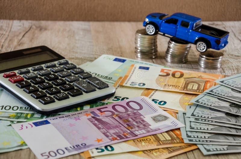 Dollar, euro, mynt, en r?knemaskin och en bl? bil f?r leksak p? en tr?bakgrund arkivfoton