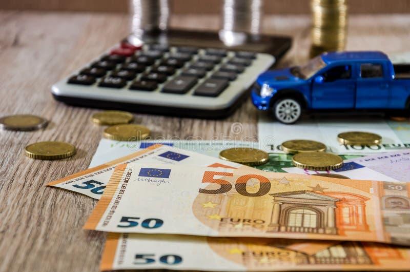 Dollar, Euros, Münzen, ein Taschenrechner und ein blaues Auto des Spielzeugs auf einem hölzernen Hintergrund stockfotografie