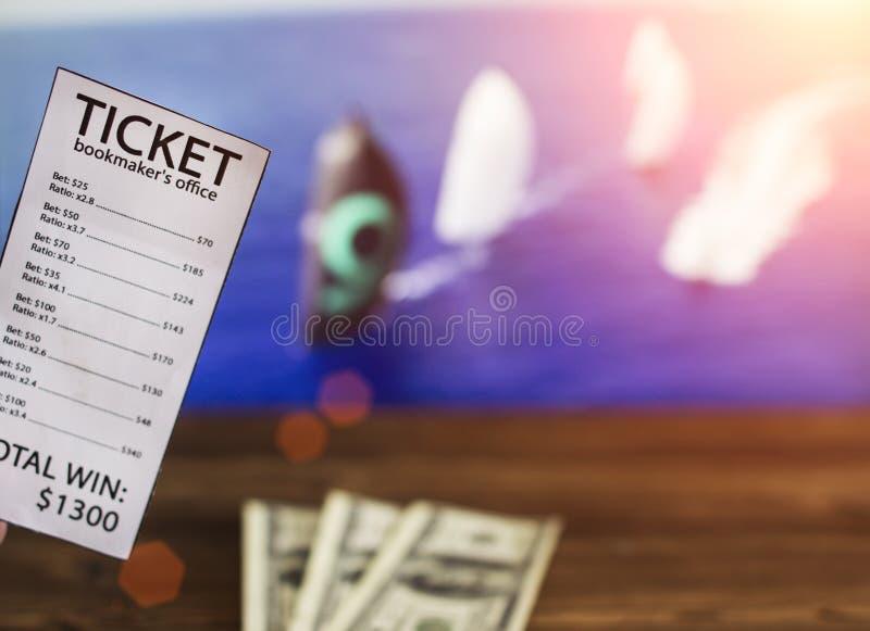 Dollar för biljett och för pengar för bookmaker` s på bakgrunden av en TV på som showsegling, slå vad för sportar royaltyfri fotografi
