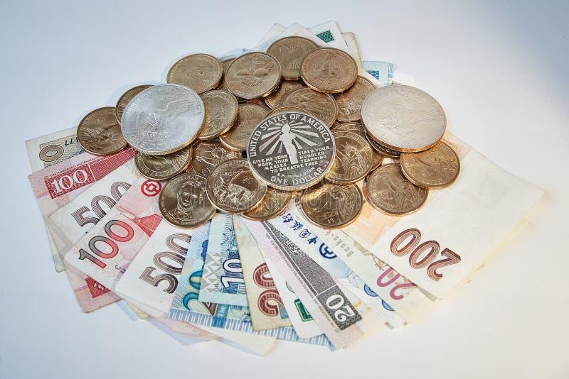 Dollar för gul och vit metall på räkningar av olika valutor, vit bakgrund arkivbild