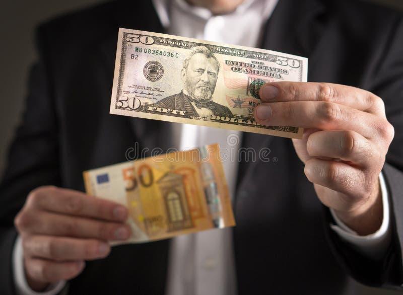 Dollar gegen Euro Geschäftsmann in der Klage, die Banknote 50 hält stockbilder