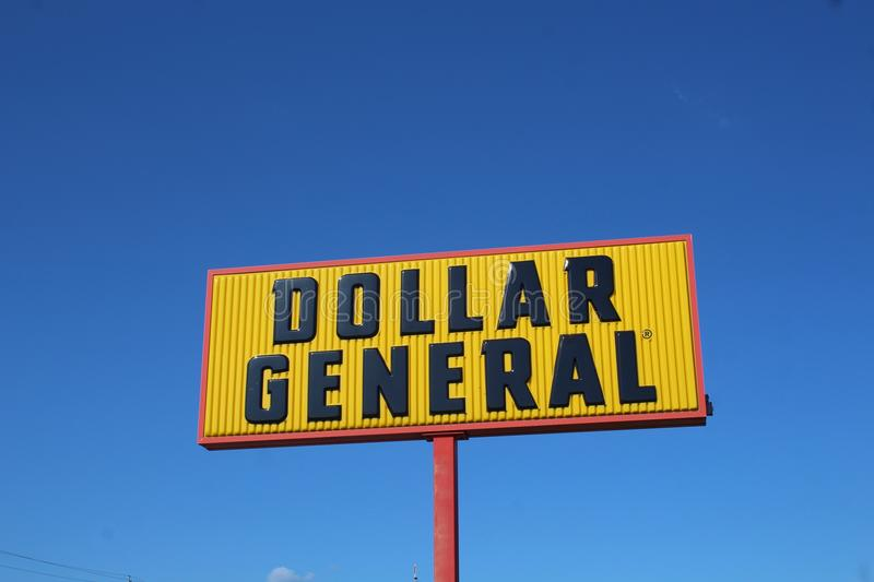 Dollar General Sign Against a Blue Sky. Dollar general is an American variety store chain. It has more than 16,500 stores in 45 states. Its distinctive logo royalty free stock photography