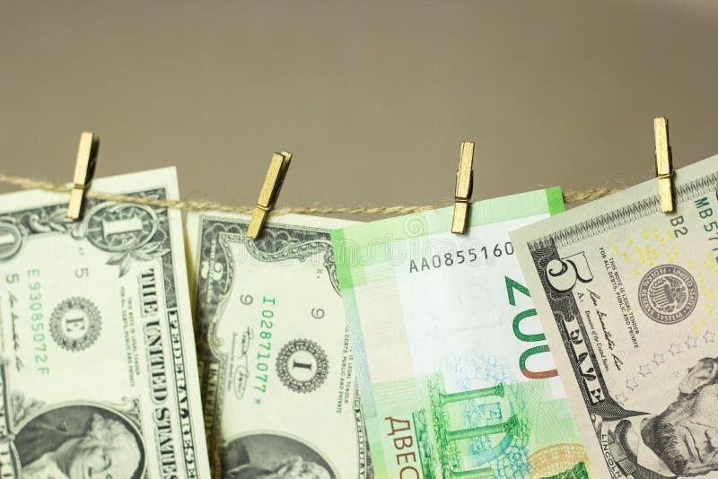 Dollar hänger på klädstreckklädnyporna som fästas på en guld- bakgrund fotografering för bildbyråer