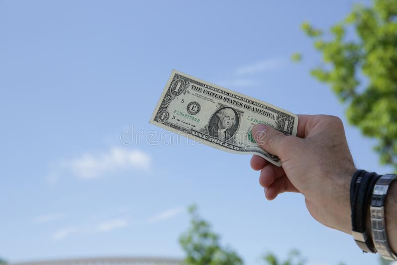 Dollar in hand against the background of blue sky and green foliage royalty free stock image