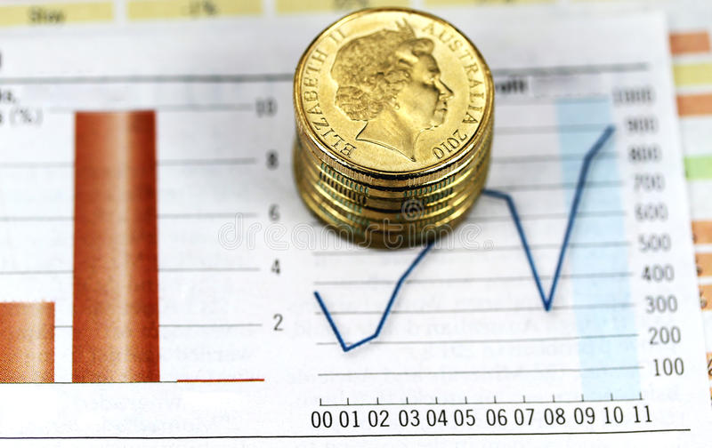 Dollar on a High. Some gold coins stacked on a newspaper graph where the trend is up, indicating that the Australian dollar is on the verge eclipsing the US stock photography