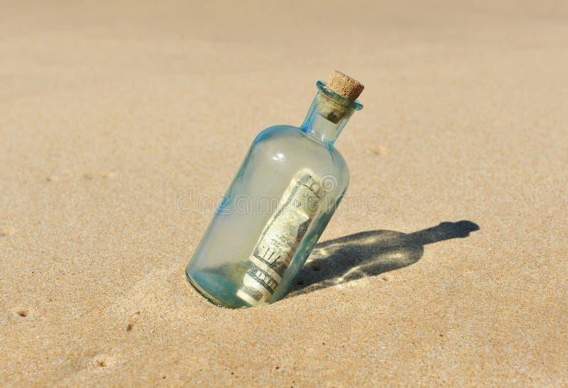 10 dollar i en flaska på sanden arkivbild