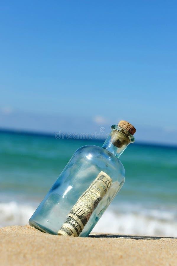10 dollar i en flaska på stranden arkivfoto