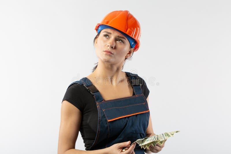 Dollar lön för sedlar för tekniker eller för arkitekt för ung kvinna hållande och tanke, betalningbegrepp på vit bakgrund arkivfoton