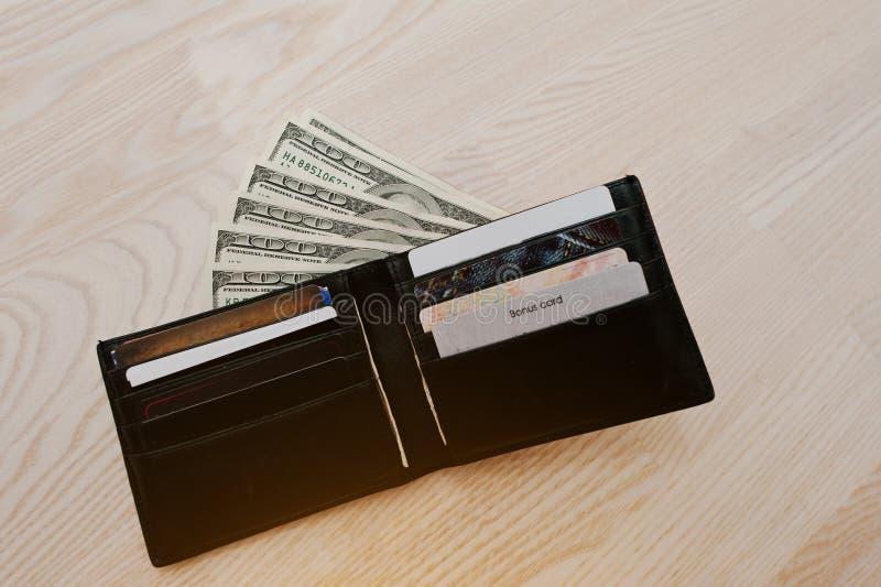 Dollar med kreditkortar i den svarta läderplånboken arkivbild