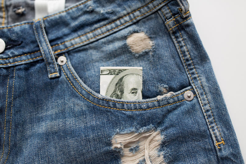 Dollar money in pocket of denim pants or jeans. Finance, clothes and currency concept - dollar money in pocket of denims or jeans royalty free stock image