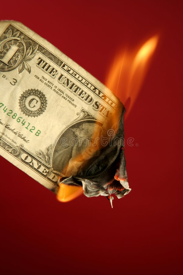 Dollar note burning in fire over red stock photo