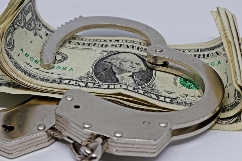 Metall handcuffs and money. Dollar notes and metall cuffs royalty free stock images