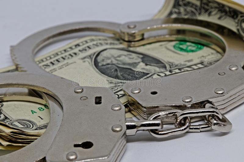 Metall handcuffs and money. Dollar notes and metall cuffs stock photo