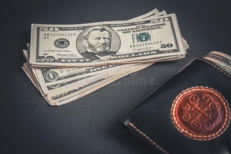 Dollar och plånbok på svart fält royaltyfria bilder
