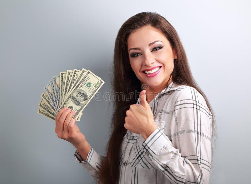Dollar och visningen för ung lycklig kvinna tummar hållande upp tecken på b royaltyfri bild