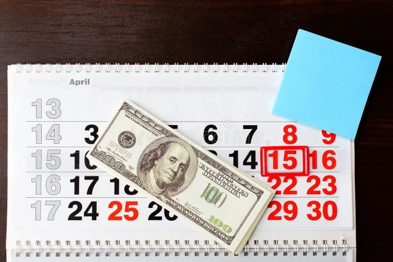 Dollar pengar och April 15 på kalendern, tomt ark av papper arkivbild