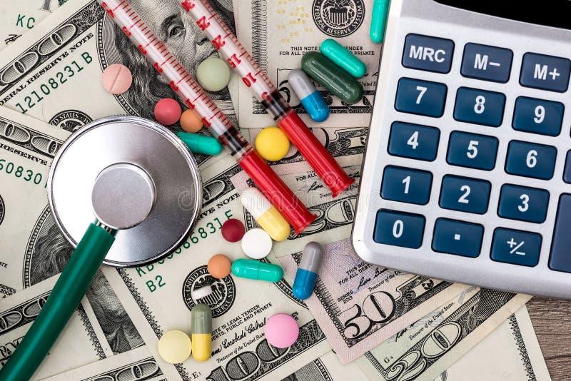 Dollar, Pillen, Spritzen, Stethoskop und Taschenrechner stockfoto